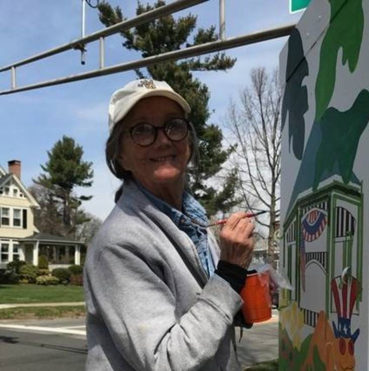 Jennifer DuTeil painting one  of the traffic boxes as part of the public arts project.